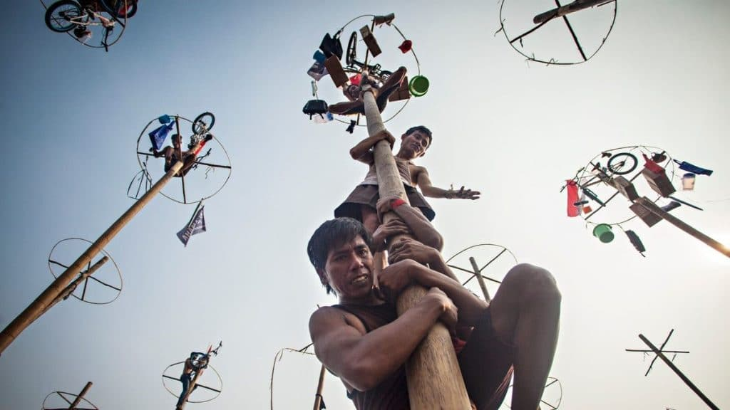 Three Indonesian Men climbing a long pole. At the top of the of the pole are various items, including a bicycle