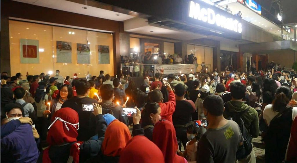 Crowd of people standing outside a McDonalds