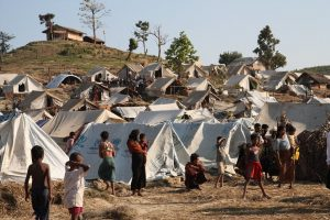 Refugees standing outside tents in internally displaced persons camp