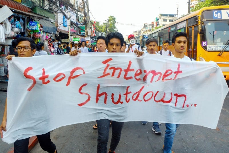 Crowd walking down street. The three people in front carry a white banner. The text on the banner reads: Stop Internet Shutdown